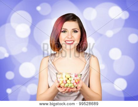 Beautiful woman in dress with a bowl of candies on bubble background.