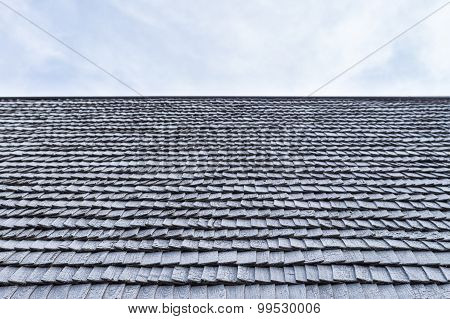 Worn Wooden Roof Shingle Of Old House Against Sky