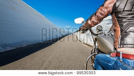 Biker girl rides a mountain road with high snow wall in Norway. First-person view.