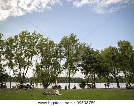 People riding their bycicles or sitting on the grass in Herastrau park