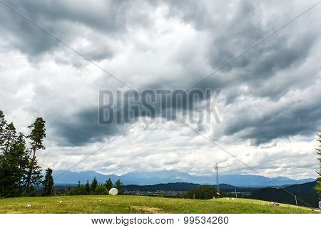 Thunderstorm Clouds Over A Green Village
