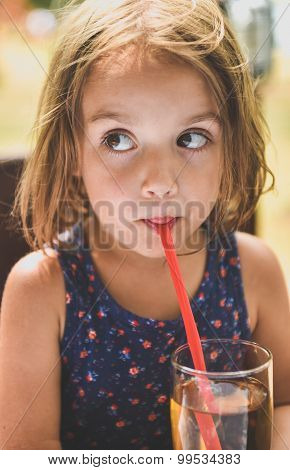 Girl Drinking Apple Juice With A Straw