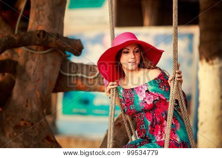 Slim Girl In Long And Red Hat Swings On Beach By Plant
