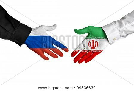 Russian and Iranian leaders shaking hands on a deal agreement