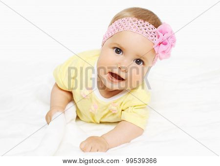 Portrait Of Cute Baby In Headband With Flower Lying