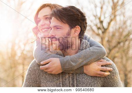 Closeup of man carrying woman piggyback at park