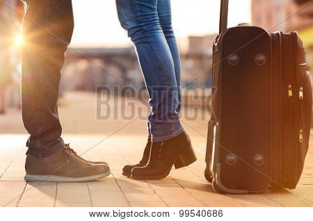 Closeup shot of woman feet standing on tiptoe while embracing her man at railway platform for a farewell before train departure. A travelling luggage is on the foreground.