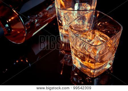Top Of View Of Glass Of Whiskey Near Bottle On Black Table With Reflection, Old Style