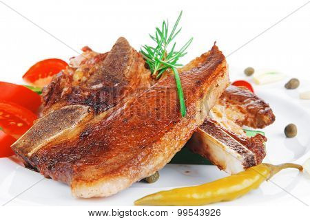 fresh grilled beef meat fillet on white plate with tomatoes and red pepper isolated  over white background . shallow dof
