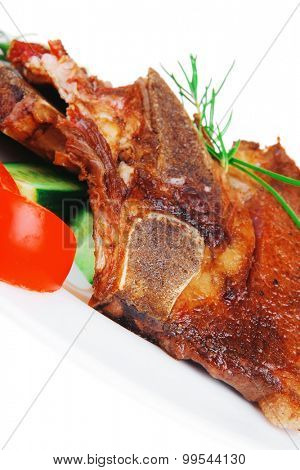 fresh roasted beef meat bone steak on ceramic dish with red hot pepper and tomatoes isolated  over white background