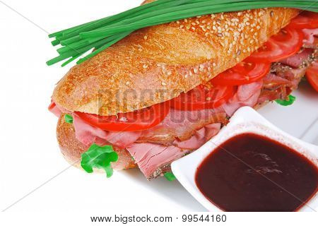 sandwich : french long baguette with smoked chicken sausage on plate with sauces isolated on white