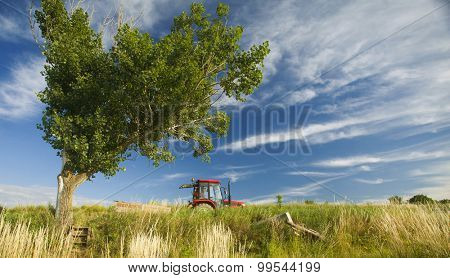 Summer rural landscape with red tractor and farmers