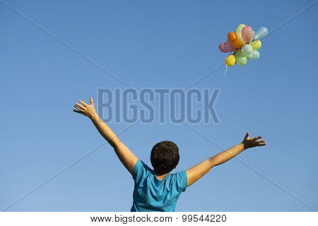 Young woman with colorful balloons in summer field