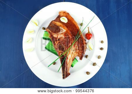 fresh grilled beef meat fillet on white plate with tomatoes and capers on blue wooden table