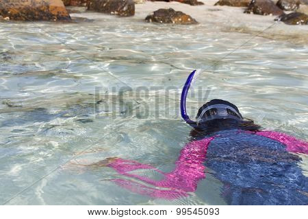Girl snorkels while heading to shore