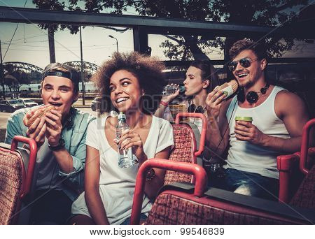 Multinational friends having snack while riding on a sightseeing bus