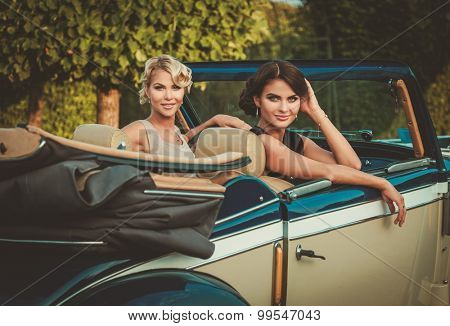 Two stylish ladies in a classic convertible