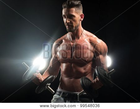 fitness male model with sixpack lifting some weights on biceps