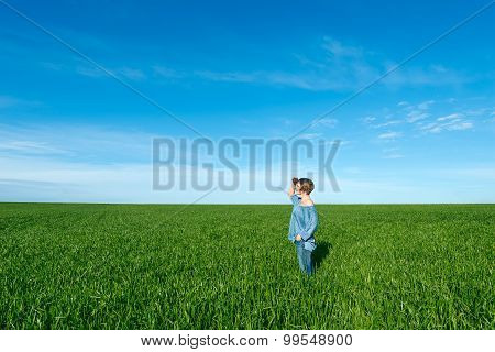 Woman Standing And Looking Far Away  In Green Field