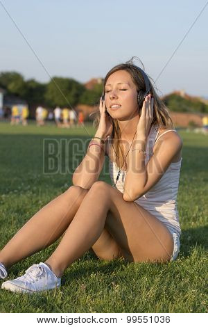 Girl Listening To Music On The Soccer Field. Training Break