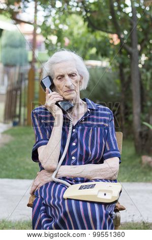 Elderly Woman Talking On The Phone In The Backyard