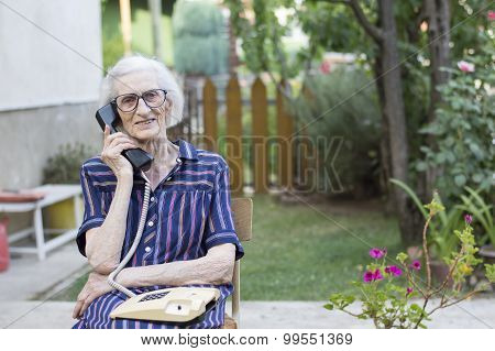 Happy Elderly Woman Talking On The Phone In The Backyard