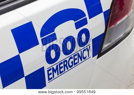 Emergency number 000 on a police car