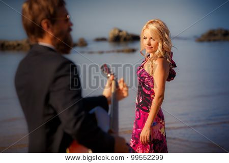 Guitarist Back-view And Blonde Girl Against Sea