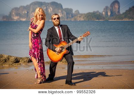 Blonde In Red And Guitarist On Sand At Low Tide
