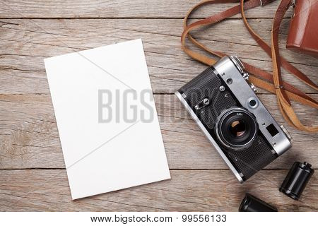 Vintage film camera and blank photo frame on wooden table. Top view