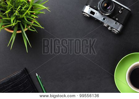 Office leather desk table with camera, supplies, coffee cup and flower. Top view with copy space