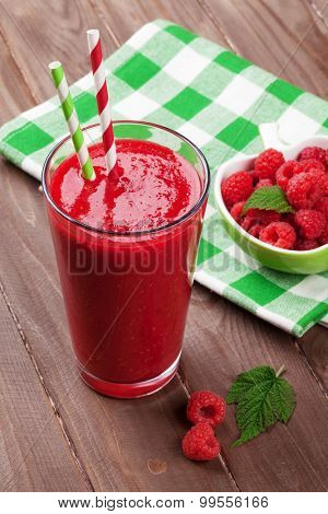 Raspberry smoothie and berries on wooden table