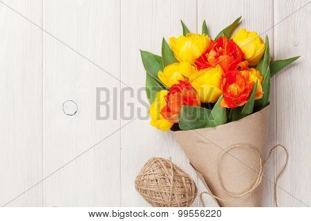 Colorful tulips over wooden table background with copy space