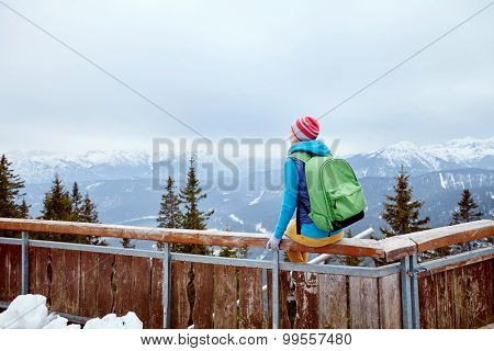 Back view of young woman wearing pink hat, blue jacket, green backpack and yellow pants sitting on wooden fence against winter mountains - adventure concept