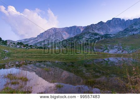 mountain with lake under blue sky