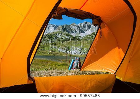 camping in mountain lake with backpack and  Nordic walking sticks