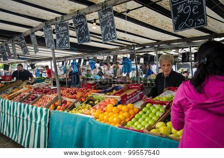 Woman shops for fresh vegetables at the Bastille market in Paris