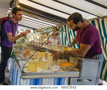 Man shops for cheese at an outdoor market in the Bastille neighborhood
