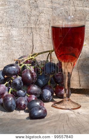 glass of red wine and blue grapes