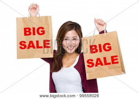 Asian woman raise up the shopping bag for showing big sale