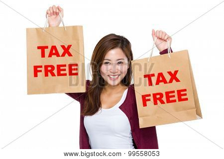 Asian woman raise up the shopping bag for showing tax free