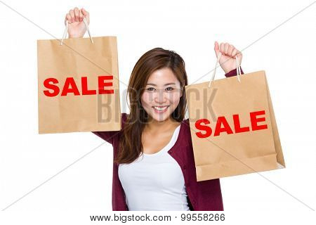 Asian woman raise up the shopping bag for showing a word sale