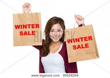 Asian woman raise up the shopping bag for showing winter sale