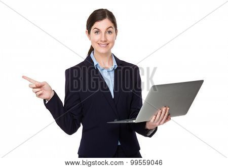 Businesswoman hold with laptop computer and finger point aside