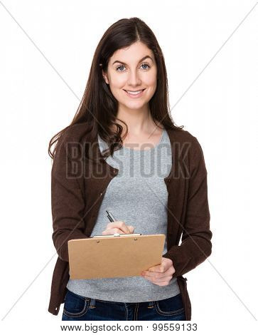 Young woman take note on clipboard