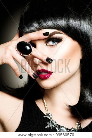 Beautiful mysterious brunette lady portrait. Beauty young woman with bob haircut, bright make up, red lips, smoky eyes makeup. Luxury accessories, ring and necklace