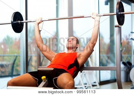 Muscular man training hard in a gym