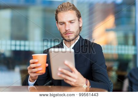 Businessman reading his digital tablet during breakfast