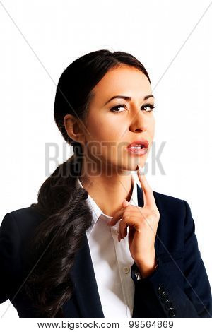 Pensive businesswoman with finger under chin.