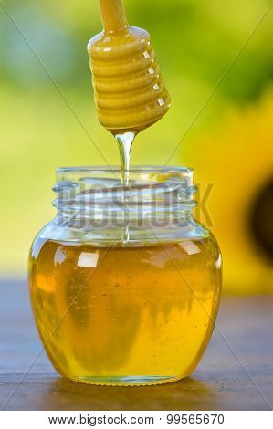 Honey Dripping Off A Honey Spoon Into A Glass Bowl.